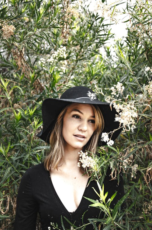 Peaceful woman standing among tall green plants in black body with long sleeve and hat and looking away in summer sunny day