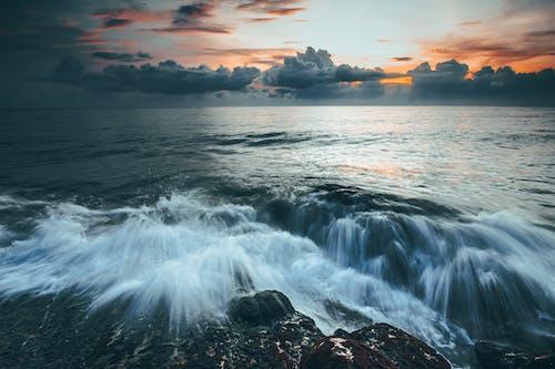 Long exposure of white foamy waves crashing over dark rocky shore of powerful ocean under dramatic overcast sunset