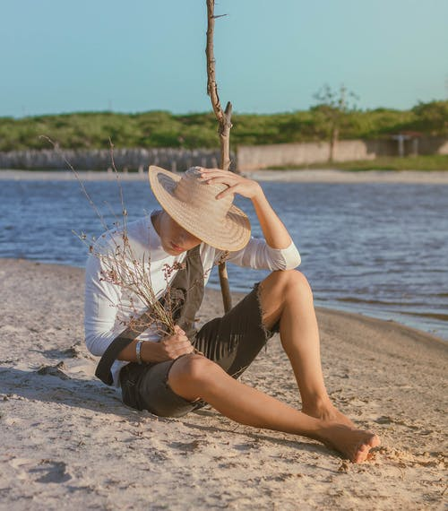 Unrecognizable man sitting on sandy coast near water