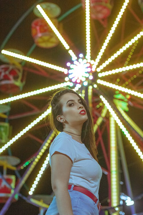 Side view of cool woman with makeup looking at camera sensually against illuminated Ferris wheel in night amusement park