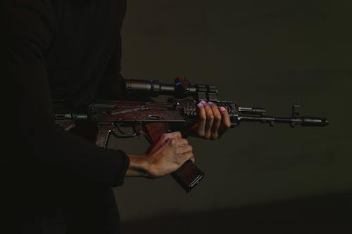 Man in Black Long Sleeve Shirt Holding Black Rifle