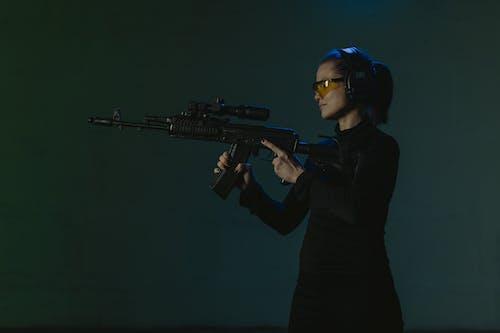 Woman in Black Long Sleeve Shirt Holding Black Rifle