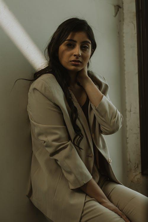 Stylish Indian woman touching neck near wall