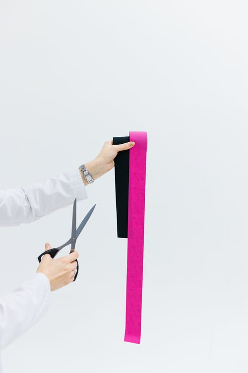 Person in White Long Sleeve Shirt Holding Pink and Black Scissors