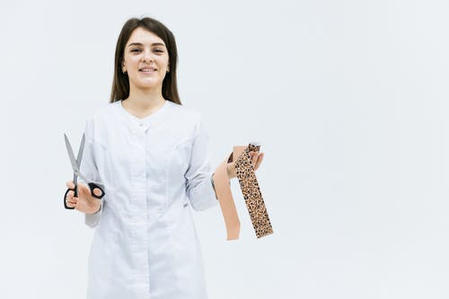 Woman in White Long Sleeve Shirt Holding Brown and Black Leopard Print Leather Bag
