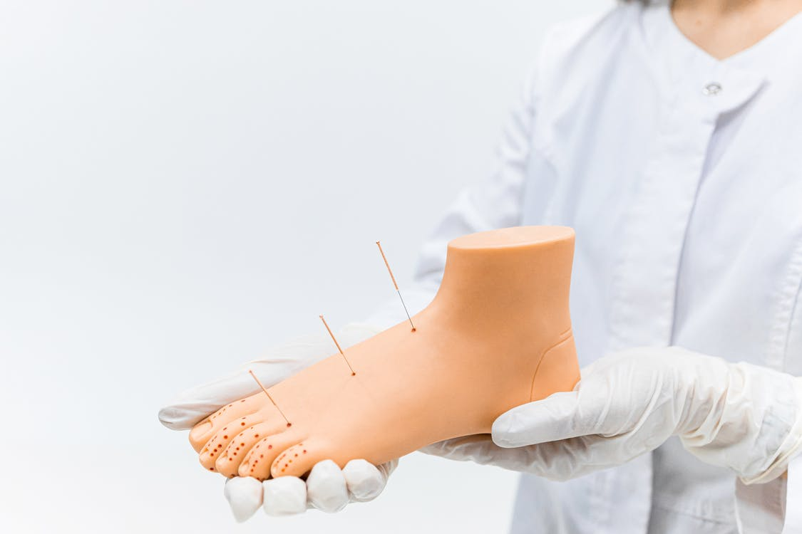 Person in White Gloves Holding White Cotton Buds