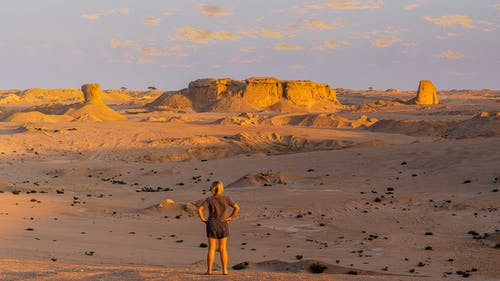 Back view of unrecognizable female traveler in casual clothes standing with hands on waist and admiring picturesque desert landscape with massive limestone cliffs at sunset