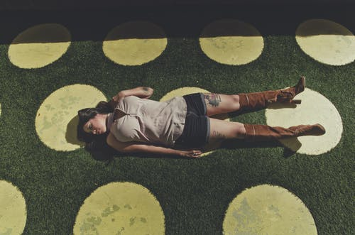 High angle full body of young woman in casual clothes and brown boots lying alone on green grass with yellow circles in sunny summer day and looking away