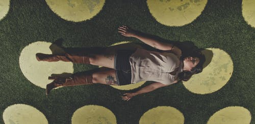 Woman lying on green meadow with grass