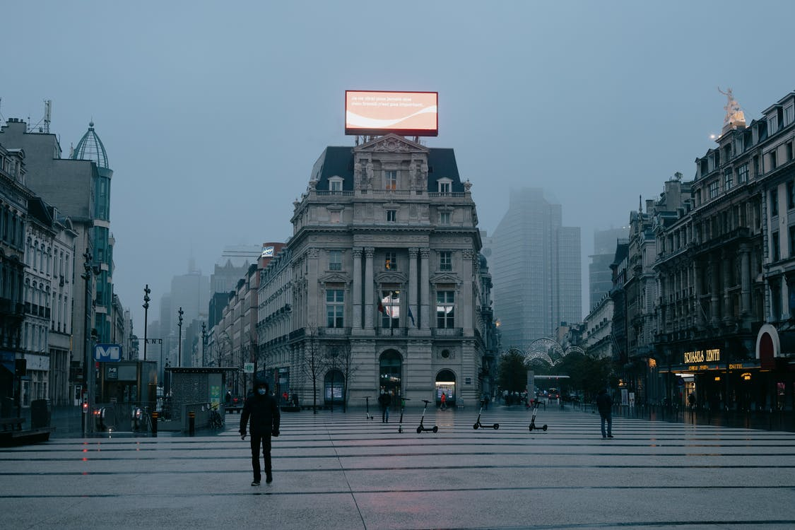 Unrecognizable pedestrians in face masks walking on city square near aged buildings against foggy sky in evening in Brussels