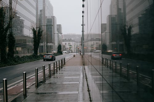 Modern city street with glass building on overcast rainy day