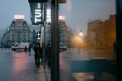 Anonymous people in medical masks walking on Place de Brouckere square near modern building with glass walls in rainy evening during coronavirus in Brussels
