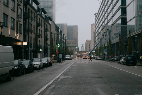 Traffic on city road among buildings on overcast sky