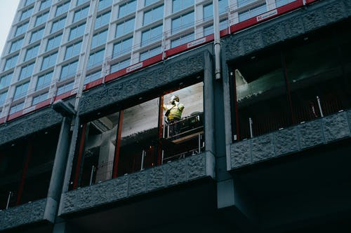 From below of unrecognizable person in protective uniform and helmet welding metal details near window in contemporary multistory building with geometric design in city