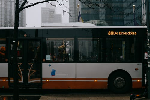 Modern bus with number and inscription on roadway against multistory building facades in city