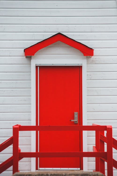 Modern house facade with red door in town