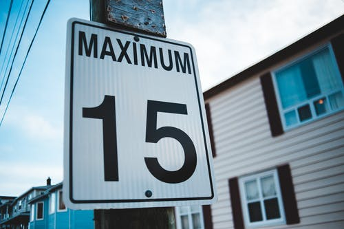 Regulatory road sign with Maximum inscription and number 15 against house facade in city in daytime