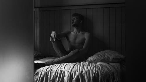 Topless Man Sitting on Bed