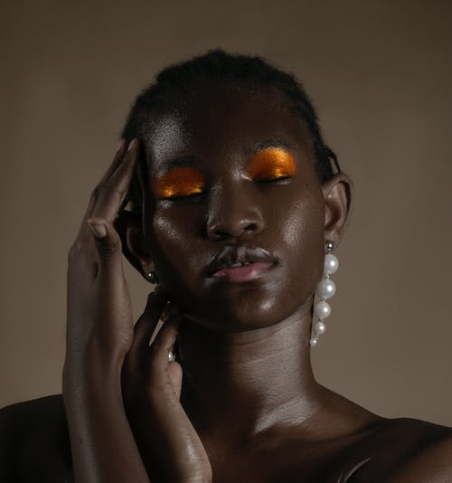 Young black female with bright glossy sparkling make up and pearl earrings touching face with closed eyes