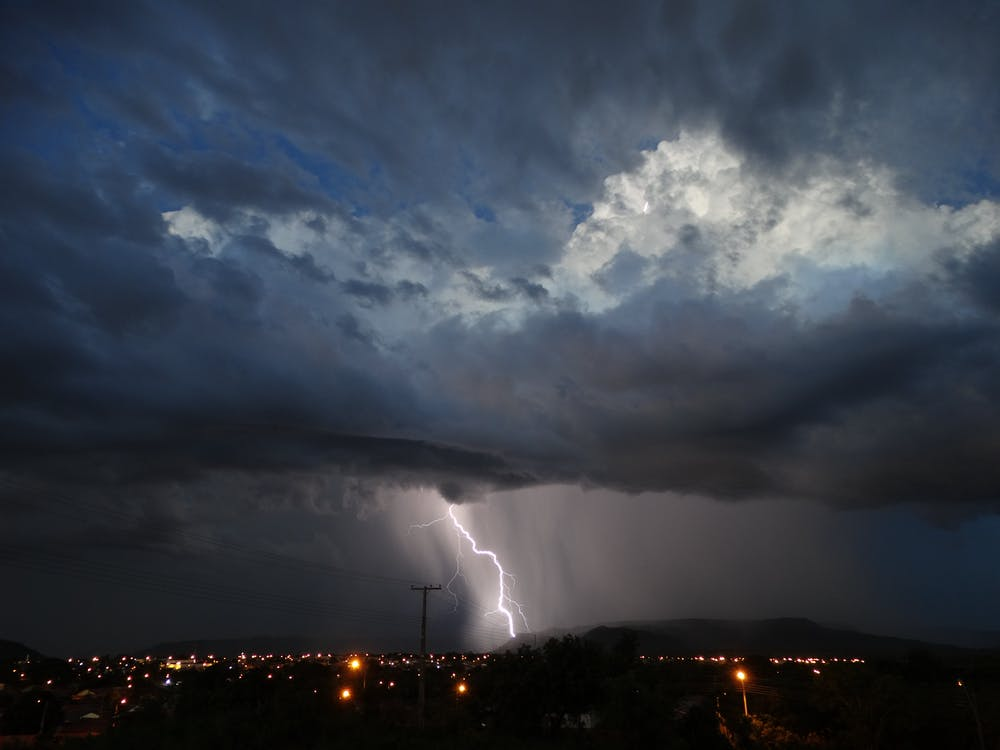 Lightning over dark city at night time
