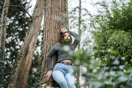 Woman in Gray Long Sleeve Shirt and Blue Denim Jeans Leaning on Brown Tree