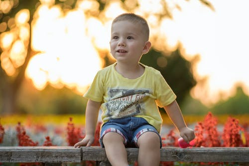 Boy in Yellow Crew Neck T-shirt Sitting on Brown Wooden Bench