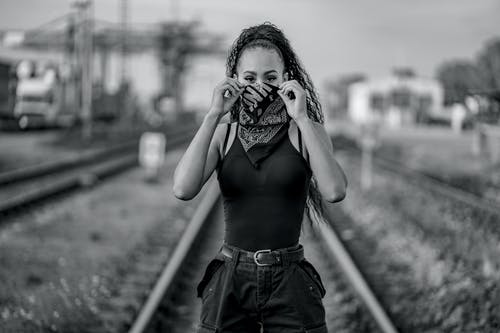 Woman in Black Tank Top and Denim Shorts Standing on Train Rail