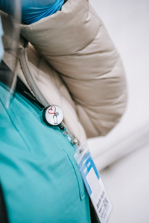 Unrecognizable woman wearing medical uniform and coat with badge on breast attached with round sign with heart and stethoscope