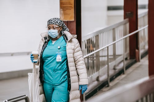 Black female nurse in uniform and protective mask on street