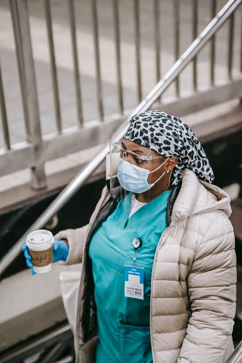 Black female nurse with paper cup going down to underground station