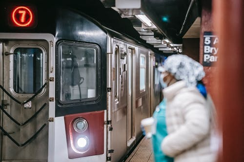 Nurse with paper cup on subway platform