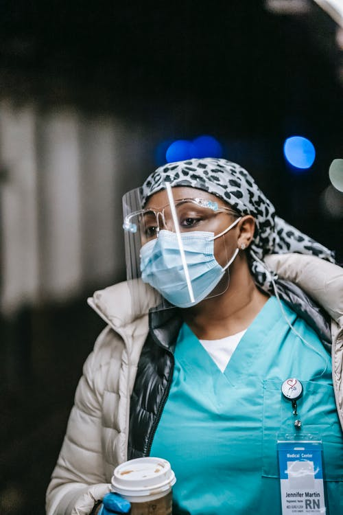 Serious black female nurse with coat and protective masks and with paper cup on blurred background
