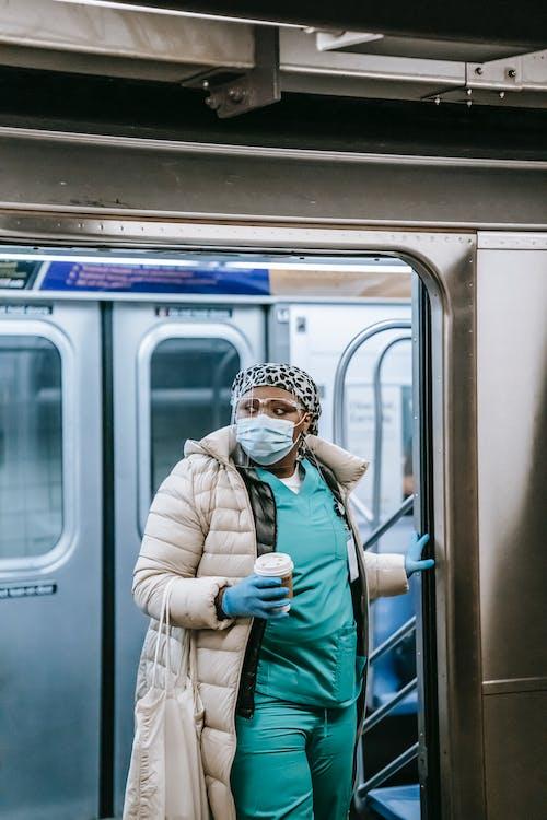 Black nurse in face mask exiting metro train