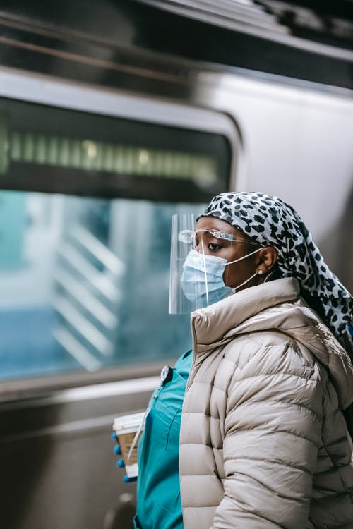 Side view emotionless plump African American female doctor in outerwear wearing mask and shield with takeaway coffee riding metro train and looking away thoughtfully