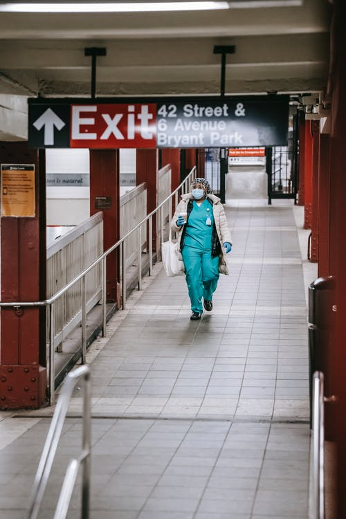 Black nurse walking in metro passage