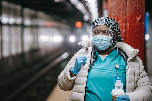 Serious plump African American nurse in uniform and outerwear wearing face mask and latex gloves standing with takeaway coffee standing on metro station platform and looking away thoughtfully