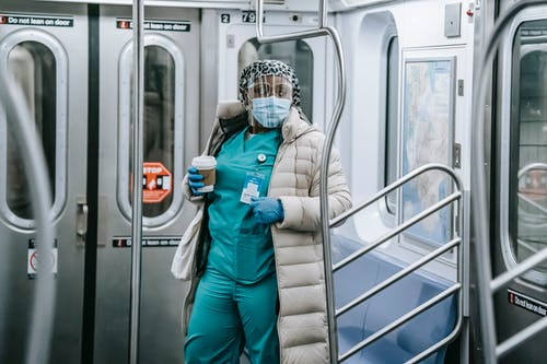 Calm African American female doctor in uniform under outerwear wearing protective mask and face shield standing with takeaway coffee in underground train