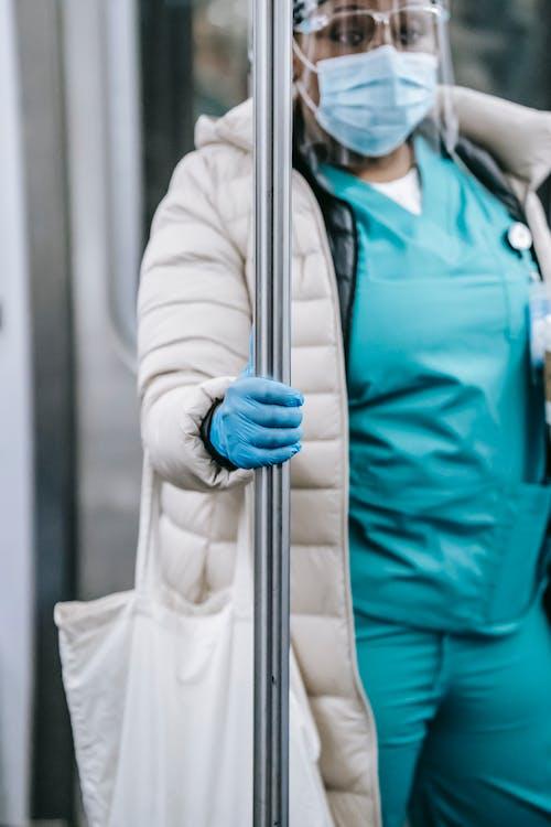 Crop black nurse in mask riding metro train