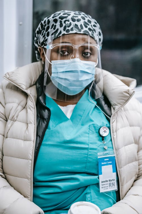 Serious African American female doctor in uniform under outerwear wearing face shield and mask riding metro train and looking at camera thoughtfully