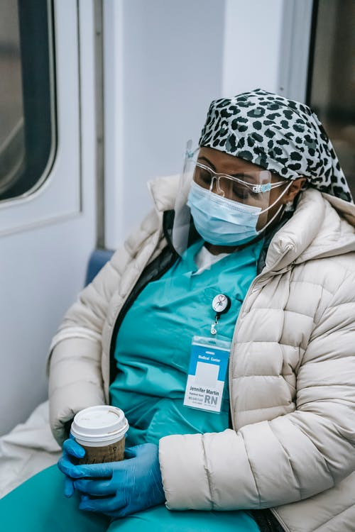 Exhausted African American nurse in warm wear and protective face shield mask and gloves sleeping in subway train after long duty during coronavirus pandemic