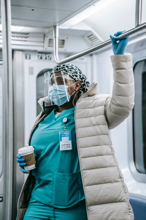 Concentrated adult African American nurse in medical uniform under warm clothes wearing mask face shield and gloves holding overhead handle and riding metro train
