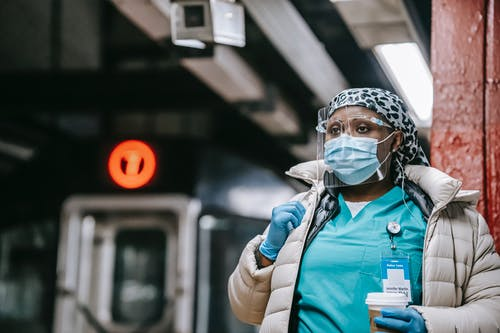 Pensive black nurse in respirator waiting for train on platform