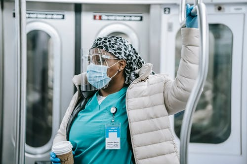 Contemplative adult African American female doctor in uniform under warm clothes wearing protective face shield mask and gloves holding handle and riding metro train