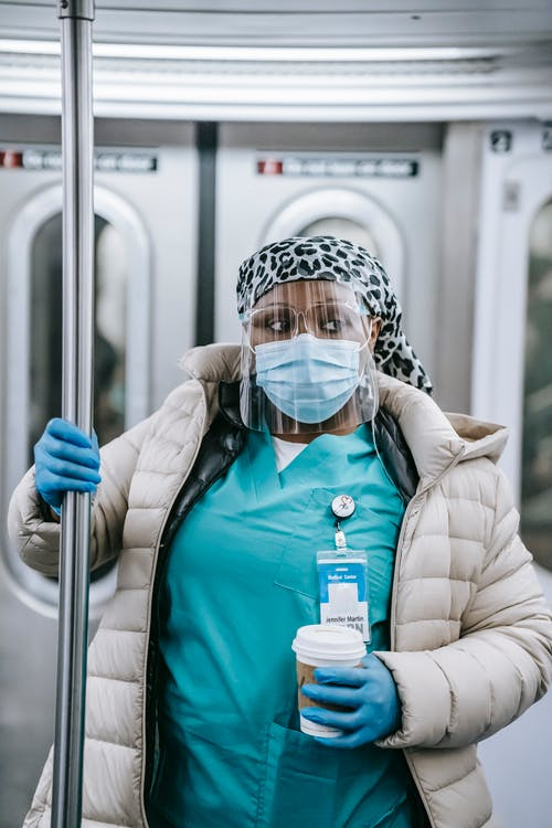 Thoughtful black nurse in mask and gloves riding metro train