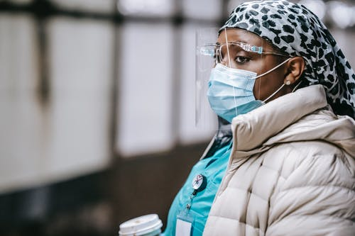 Calm adult African American female doctor in outerwear and protective mask and face shield waiting for train on underground platform and looking away pensively