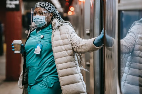 Thoughtful black nurse in protective mask leaving metro train