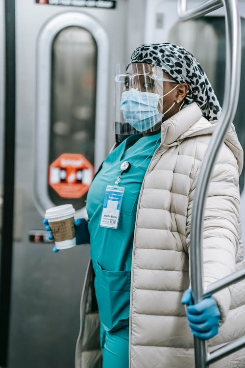 Concentrated black nurse in face shield riding metro train