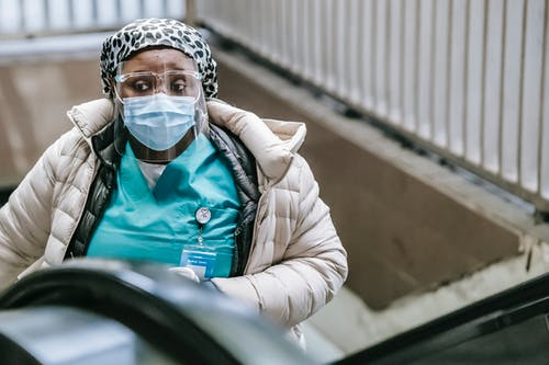Black nurse in mask riding escalator in underground
