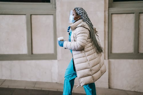 Side view calm adult African American nurse in uniform and warm clothes wearing medical mask face shield and latex gloves walking with coffee to go on street