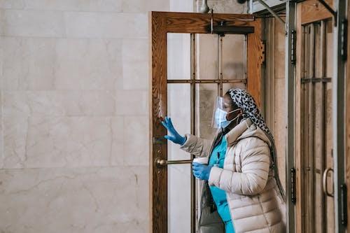 Black nurse in respirator and gloves leaving modern building